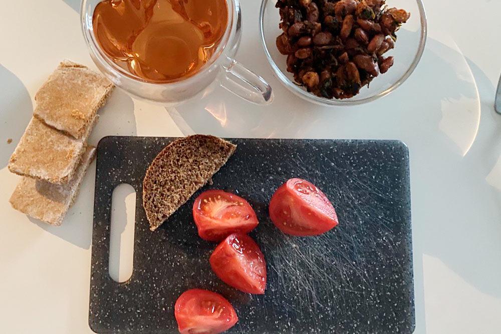 Разогреваю лобио — мы его готовим сразу много, хватает на 3—4 дня. Нарезаю хлеб, который К. испекла сама, и узбекский помидор