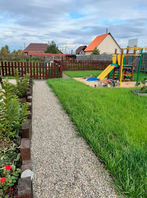 Дорожка перед домом и детская площадка, за забором — огород