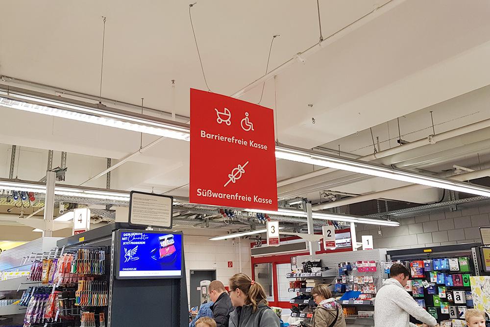 Касса в «Кауфланде», приспособленная дляпроезда детских колясок и людей с ограниченными возможностями. А еще на ней нет сладостей — это знак дляродителей с детьми, которые постоянно просят на кассе купить что-то вкусное