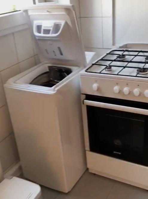 На кухне стояла небольшая стиральная машина с вертикальной загрузкой