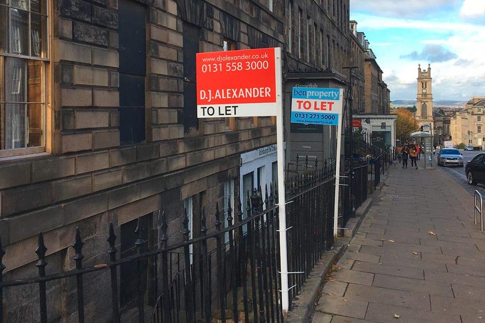 У входа в дом размещены объявления от агентств недвижимости: здесь сдается или продается квартира