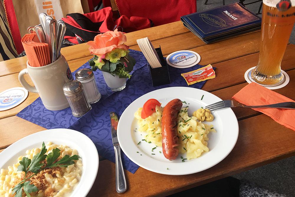 Слева традиционное баварское блюдо кэзешпетцле — домашняя лапша с сыром и сушеным луком. Зимой очень согревает. Стоит в среднем 8€ (560 рублей). Сосиски часто подают с холодным картофельным салатом, стоит такая порция 10€ (700 рублей)