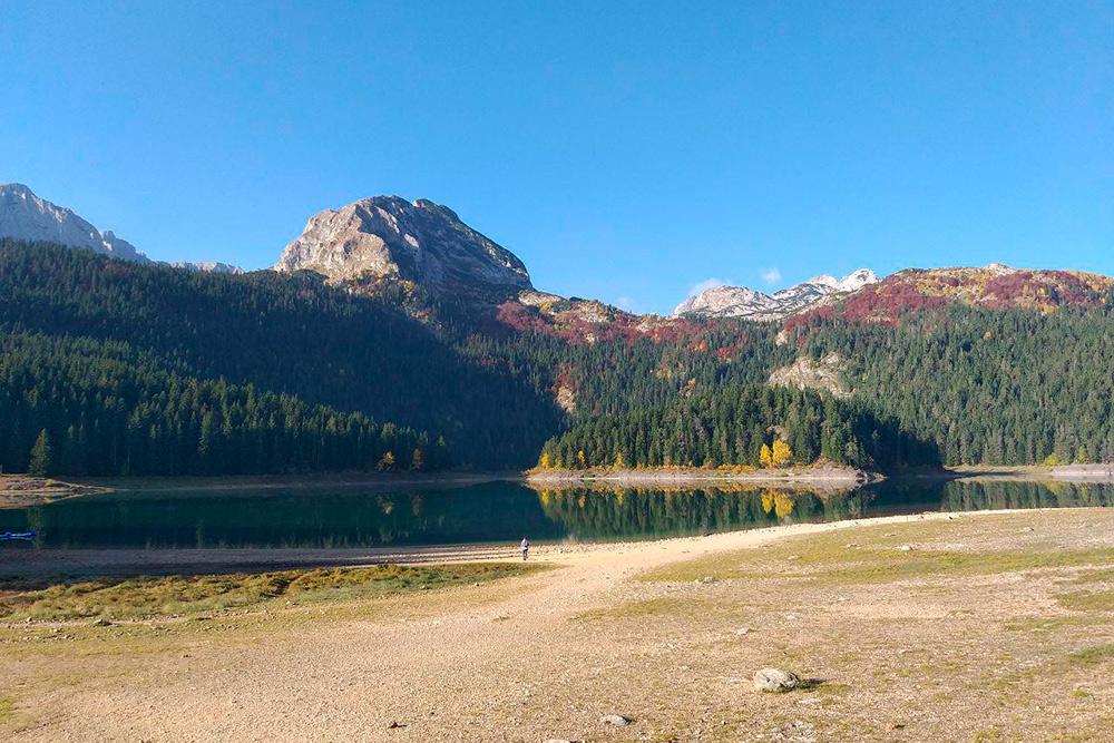 Масштаб озера и гор можно оценить, если присмотреться к маленькому человеку в середине кадра