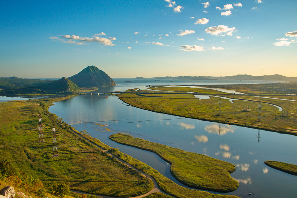 Вид с горы каждый раз разный: ширина реки, цвет деревьев и море меняются из сезона в сезон. Но всегда завораживают. Источник: russal / shutterstock.com