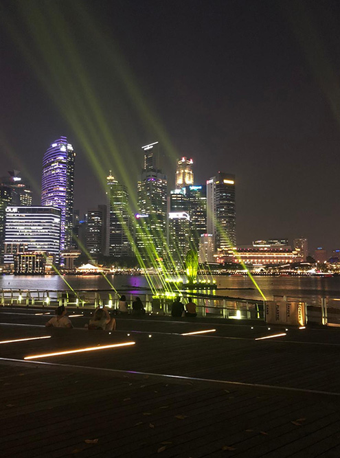 С набережной открывается вид на вечерний город и лазерное шоу