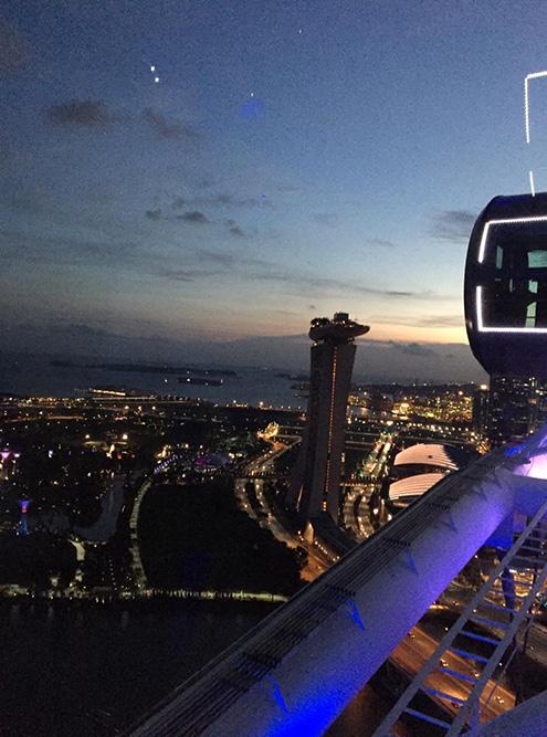 Вид на ночной Сингапур из кабинки колеса обозрения. Освещение делает и так красивый город еще лучше