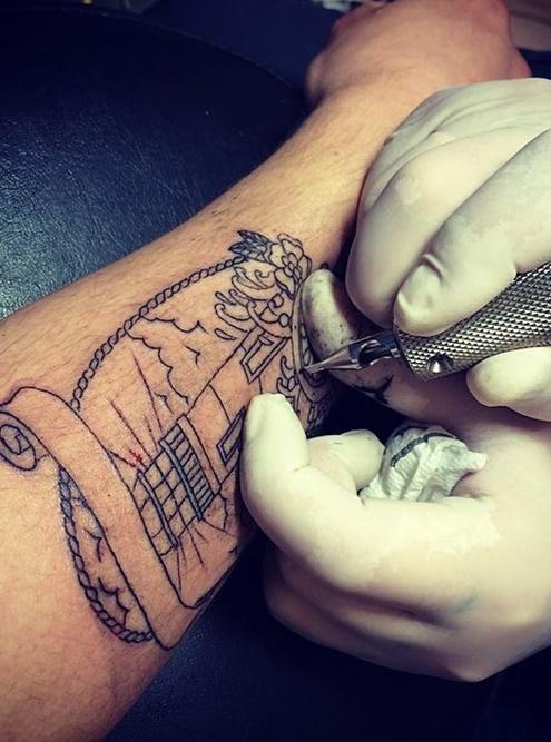 Татуировку маяка мастер начал с контуров