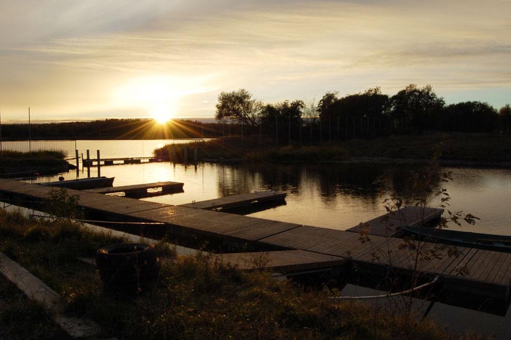 База отдыха стоит на берегу реки. Это удобно для рыбаков и владельцев небольших судов: на территории базы есть закрытая стоянка и причал для лодок. Зимой можно держать лодки в охраняемом ангаре