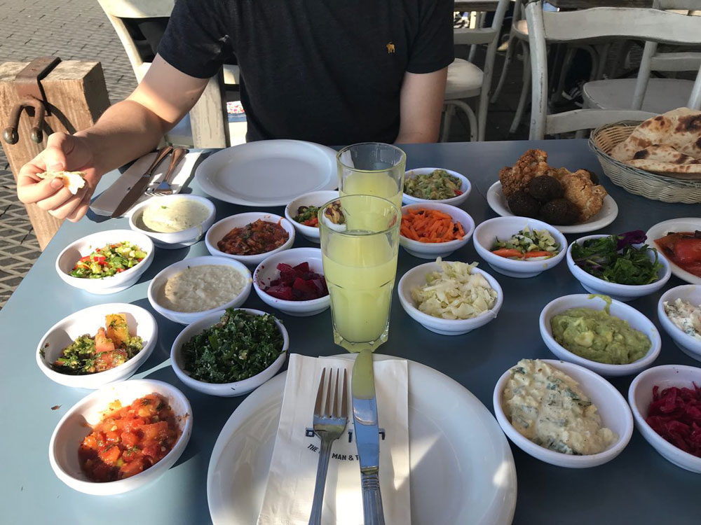 Традиционное израильское мезе выглядит так. Все эти закуски с лепешками приносят до основного блюда