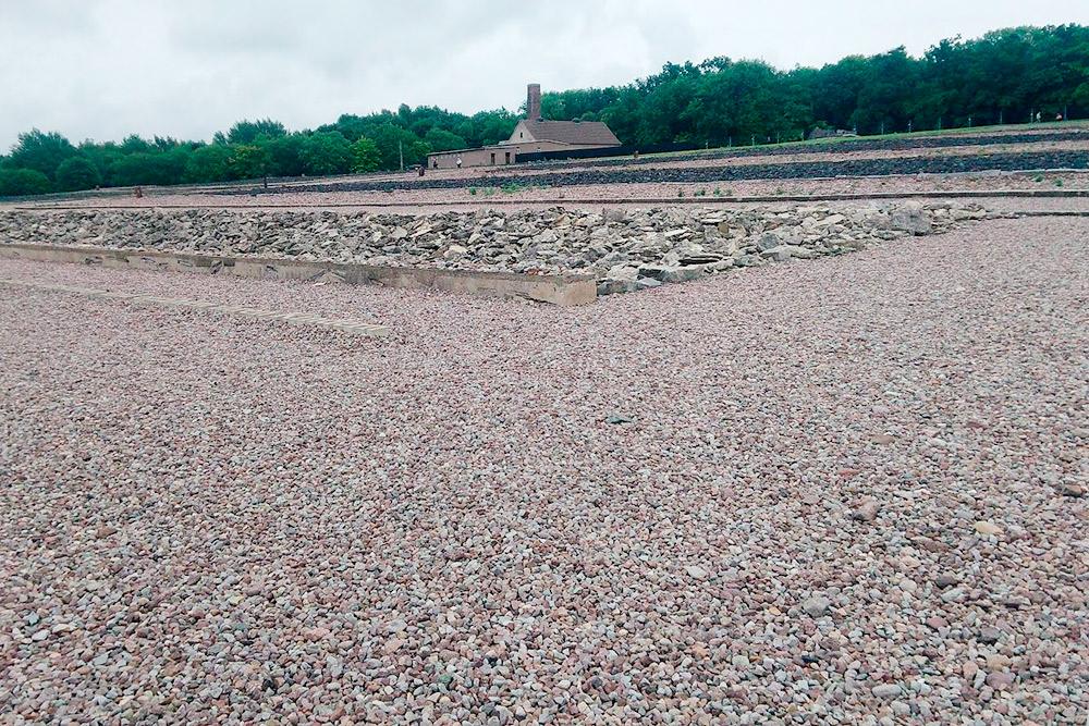 Бухенвальд сейчас выглядит так. Когда его превратили в мемориал, места бараков обозначили камнями. На заднем плане видно здание крематория. По работе я оказывалась в этих местах больше десяти раз, и там всегда была промозглая погода. Жуткое место
