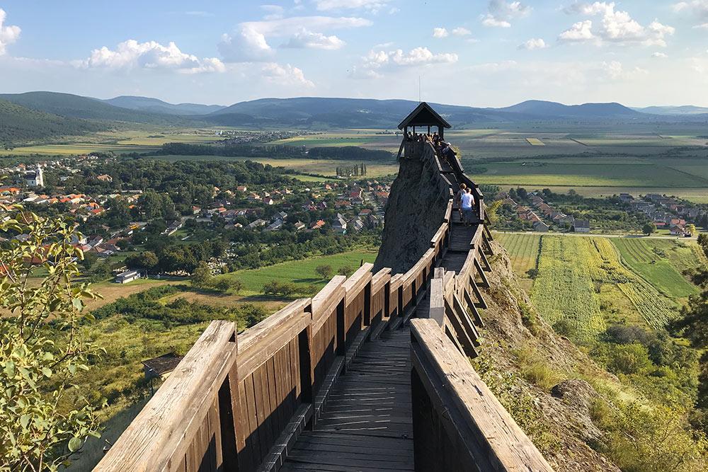 К сторожевой башне ведет длинная узкая деревянная дорожка. Обычно наэтом месте выстраивается очередь дляфото. Этабашня мелькает навсех туристических промороликах оВенгрии