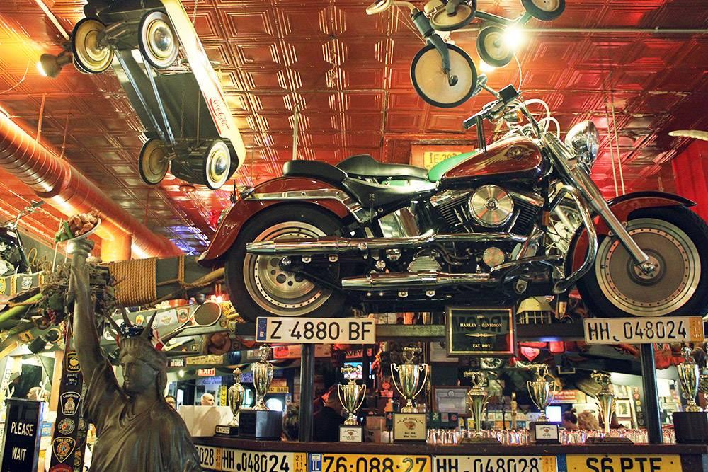 Интерьер бара напоминает музей: всюду мотоциклы и машины, автомобильные номера, значки и трофеи. К факелу статуи Свободы прилепили тарелку скуриными крылышками — это тоже символ Америки