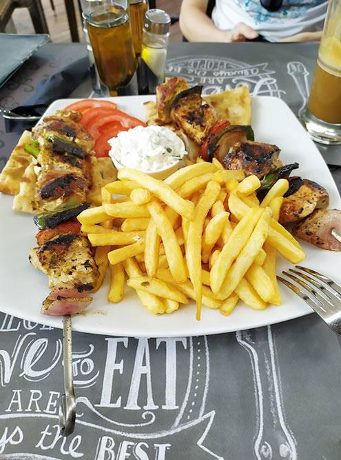 Сувлаки — греческий шашлык, подается с картошкой фри. Такая порция еды стоит 8€
