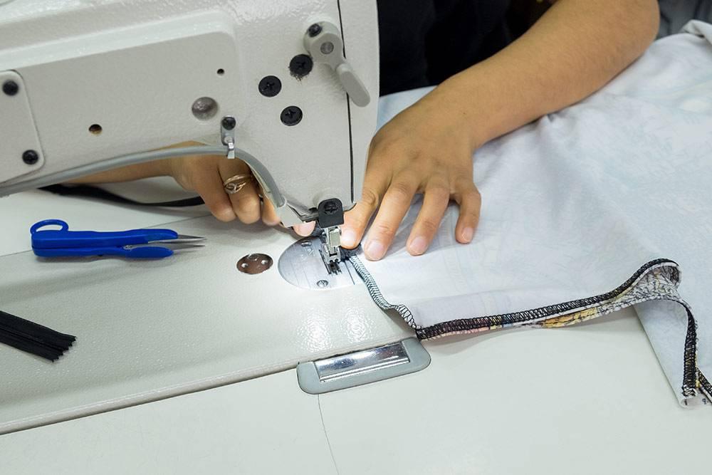 Швея сшивает разрезанные детали, получается чехол для чемодана