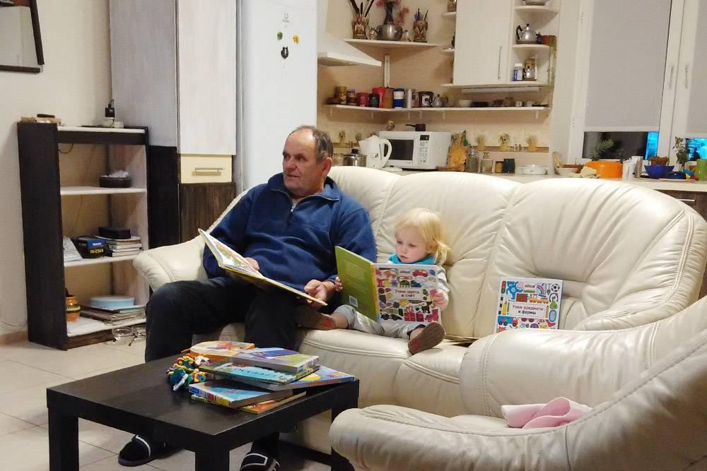 Мой отец с внучкой читают в гостиной дома в Новой Москве