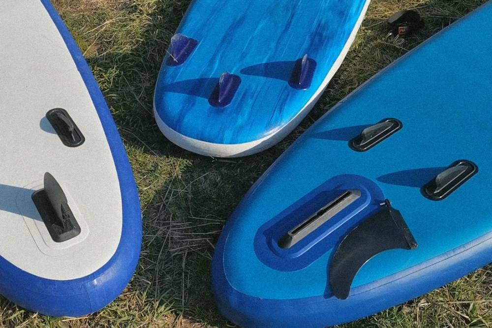 У сапа справа есть большой центральный съемный плавник и два маленьких. У сапа слева — небольшой центральный съемный плавник и два маленьких. У доски в центре все три плавника маленькие и несъемные. Из представленных вариантов лучшим будет сап справа. Источник: youtube.com