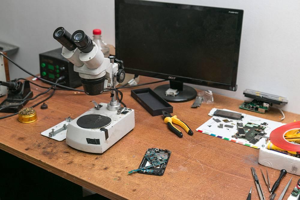 Основной рабочий стол Сергея: на нем инструменты, микроскоп, паяльник, монитор, блок питания, мультиметр. Есть еще 4 стола с разобранной техникой