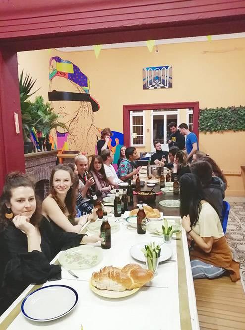 Начало ужина в хостеле: волонтеры и гости собираются за одним столом