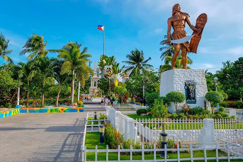 Справа — памятник Лапу-Лапу, а на заднем плане рядом с флагом — Магеллану. Источник: CHANG HYUN / Shutterstock