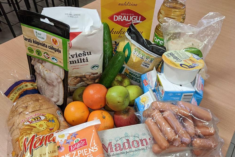 В этот раз в продуктовом пакете сосиски, десяток яиц, творог, батон, яблоки, апельсины, свежий огурец, молоко, плавленый сыр, кукурузная крупа, квашеная капуста, растительное масло, кукурузные палочки, мука и нарезка из свинины горячего копчения в вакуумной упаковке