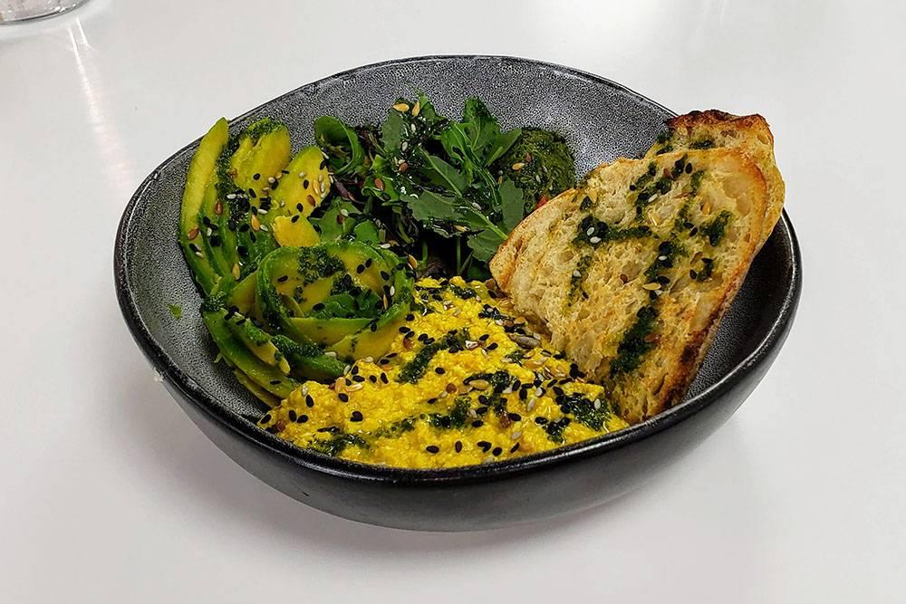 Зеленый боул с авокадо, скрэмблом из тофу, миндальной рикоттой и песто из базилика и кешью. В реальности блюдо больше, чем кажется на фото. Если вы не очень голодны, оно может заменить полноценный обед