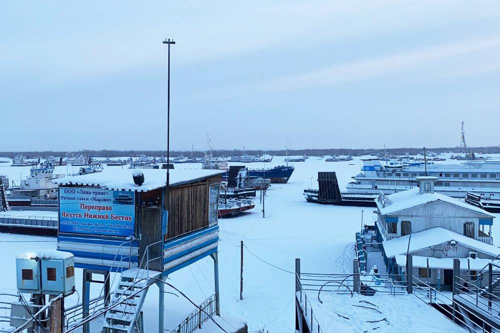 Так выглядит паромная переправа через Лену зимой. Справа стоит пассажирский теплоход, который летом возит туристов на Ленские столбы