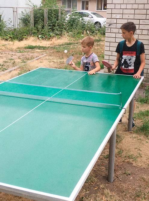Дети учатся играть в настольный теннис во дворе дома