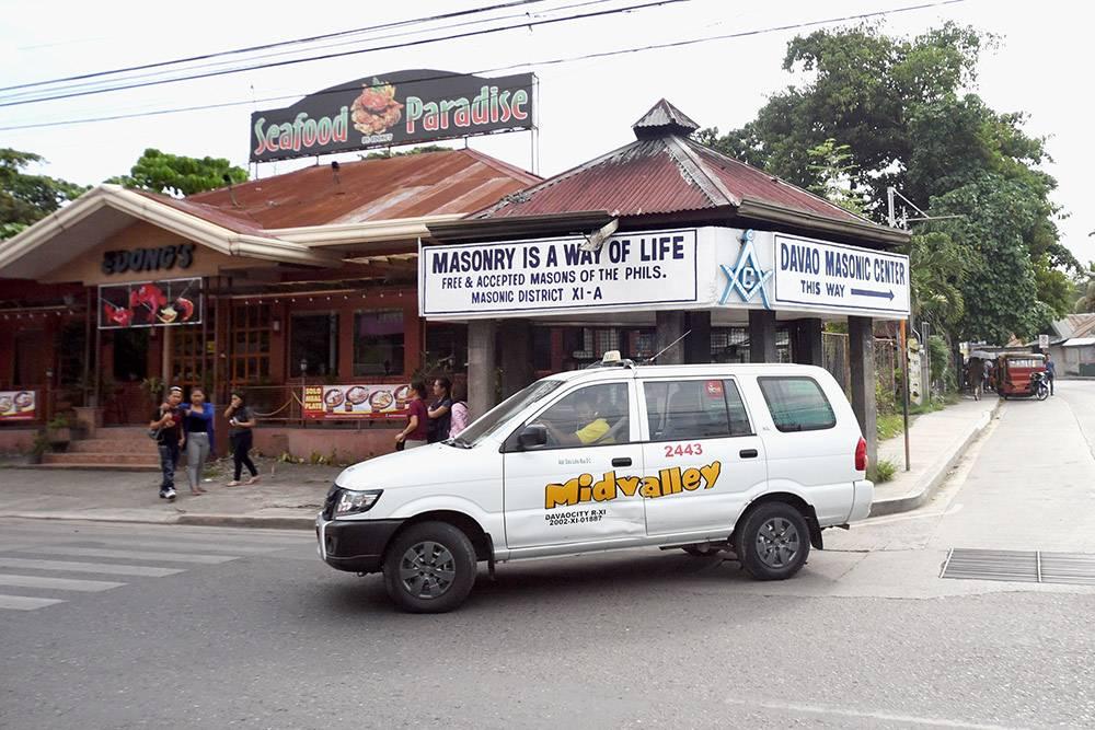 Такси на фоне указателя Масонского центра