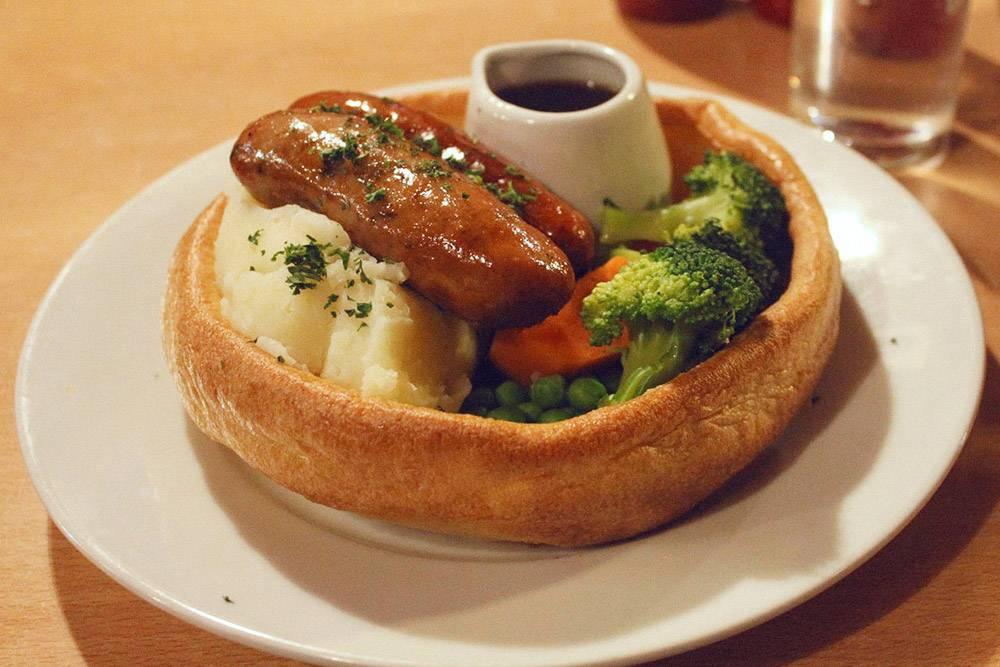 Это блюдо называется Toad in the hole и дословно переводится как «жаба в норке». «Тарелка» сделана из йоркширского пудинга — и это самая вкусная часть блюда
