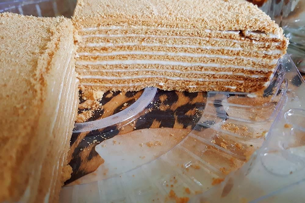 Разрез торта «Рыжик». Он непохож на популярные классические торты по вкусу или текстуре. У «Рыжика» нежный сливочный крем прослаивает многочисленные тонюсенькие рассыпчатые коржи. Можно сравнить его с миксом классических тортов «Наполеон» и «Медовик»