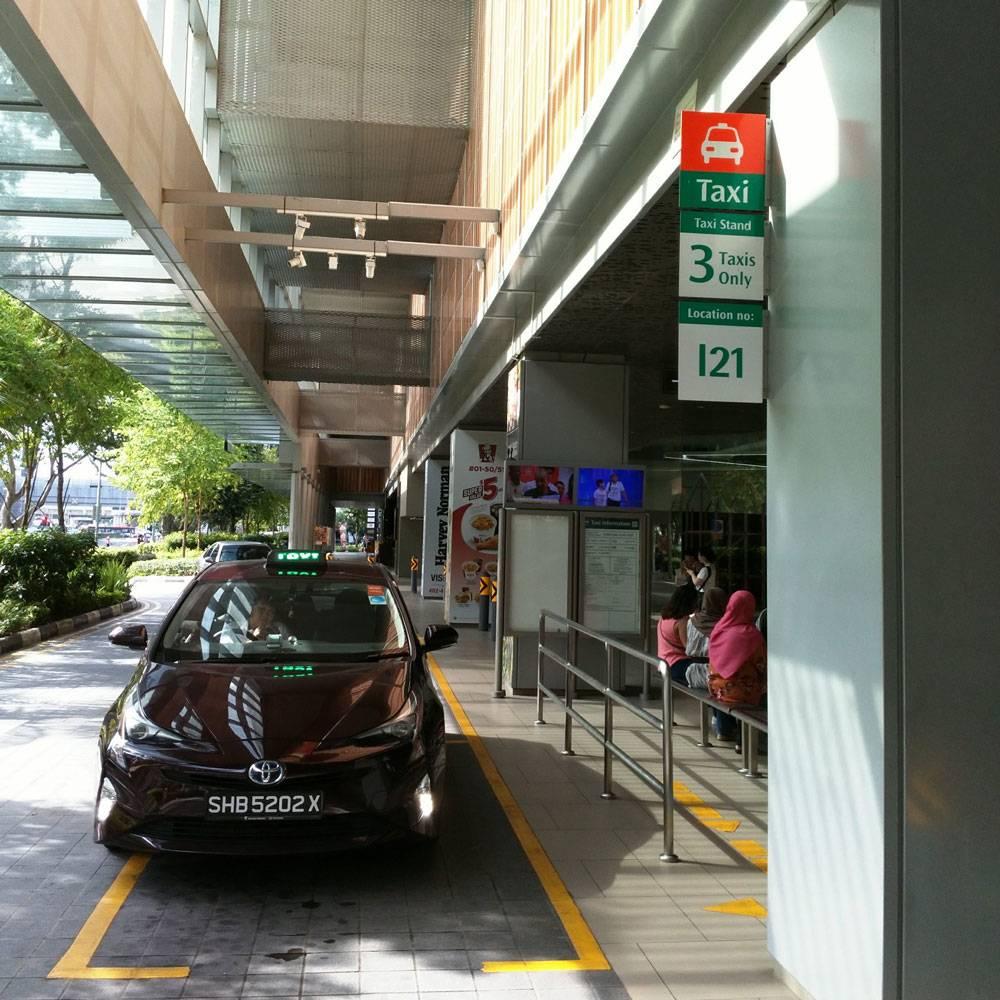 Специальный выход из торгового центра, где люди в очереди ждут такси