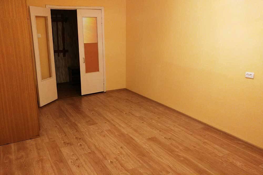 Фото одной из комнат, состояние которой было лучше, чем у остальных. Отремонтированы пол и стены. Двери в комнату старые, но теперь белые и чистые. Только электропроводка не первой свежести