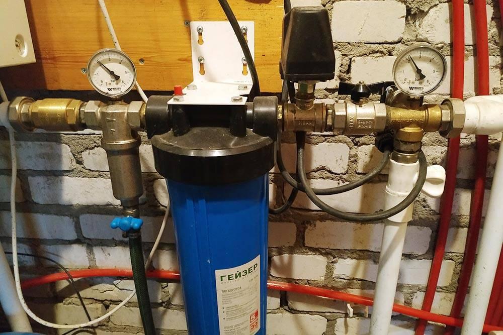 Автоматика и фильтры. Расширительный бак стоит слева внизу. В синей вытянутой колбе — нитчатый фильтр водоочистки. Перед ним слева — самопромывной фильтр. Манометр надним показывает давление насоса, черная коробочка прячет реле защиты от сухого хода, правый манометр показывает давление в расширительном баке и в системе внутри дома. Если показания двух манометров сильно различаются, пора менять фильтрующие элементы. За правым манометром вертикально стоит реле пуска и регулирования