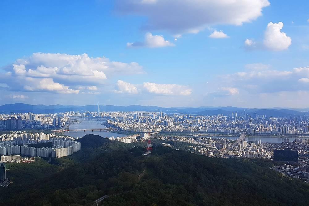 Панорама Сеула со смотровой площадки. Вдалеке виднеется огромный небоскреб World Lotte Tower