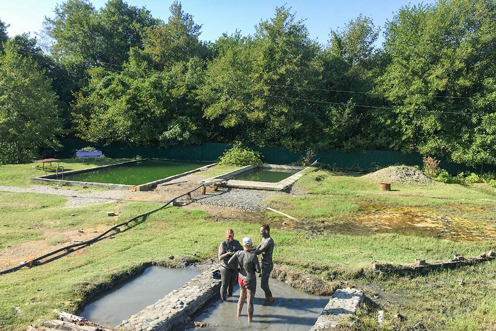 На фото видны два бассейна, в которые идет шланг с горячей водой, и ванны с грязью на переднем плане