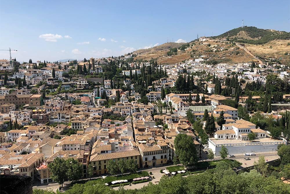 С крепости Альгамбра видно дома с белыми стенами и овальными окнами. Они напоминают здания в арабских странах