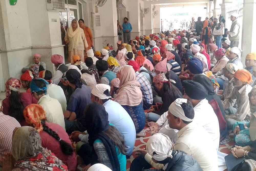 Толпа ждет бесплатного обеда перед столовой сикхского храма в Дели