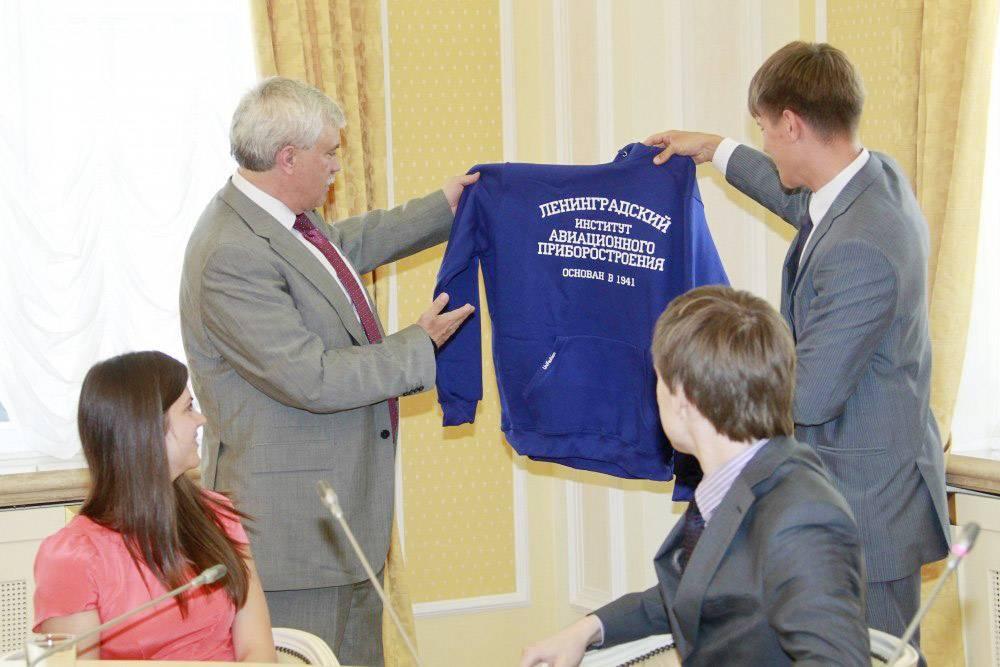 Семен дарит губернатору Петербурга Георгию Полтавченко толстовку с названием вуза, который тот окончил