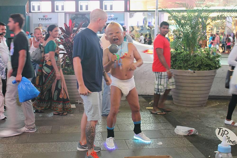 Мужчина в обличье страшного ребенка берет деньги на чай за фото. Справа к детской бутылочке прикреплена надпись: «Чаевые, пожалуйста»
