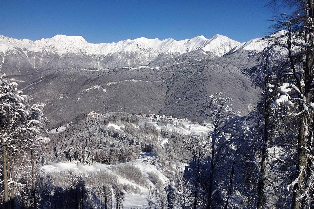 На этой фотографии сразу два горных курорта. Чуть ближе видна горная Олимпийская деревня «РозыХутор», чуть дальше, подбелыми шапками гор, — трассы «Газпрома»