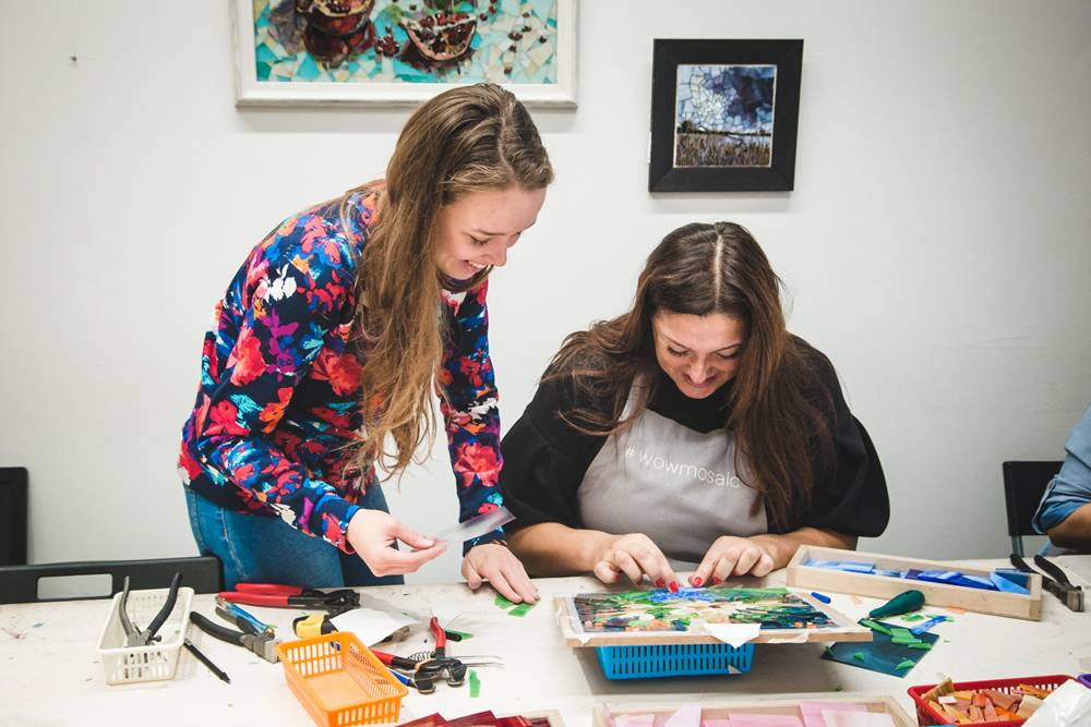 Преподаватель помогает ученице закончить мозаику