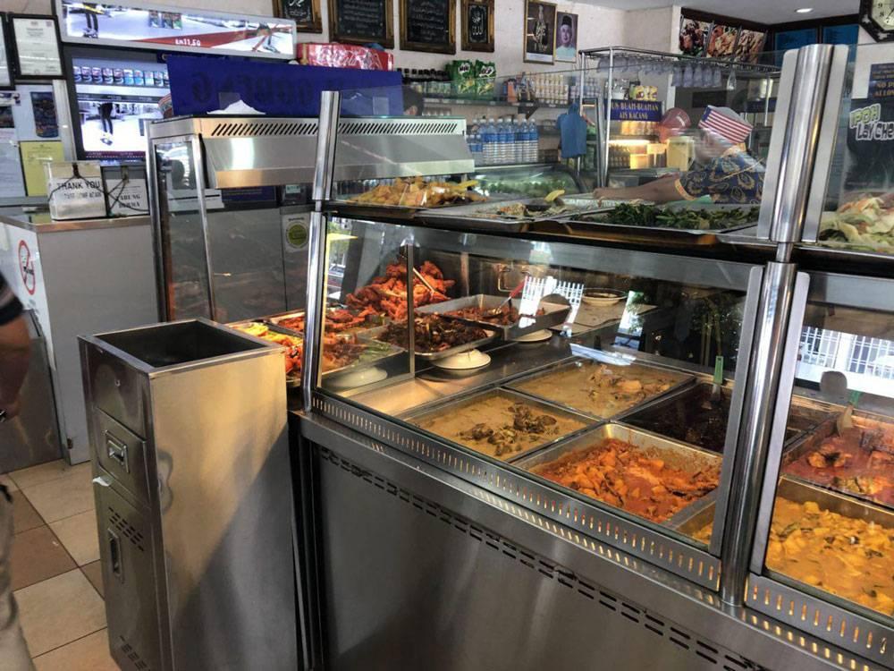 Витрина с жареными овощами в традиционной малайзийской кафешке. Покупатели сами накладывают еду, выбирают напитки и оплачивают свой поднос на кассе