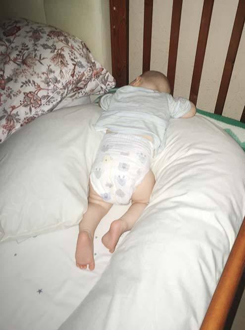 Сын спит уже в своей кроватке, которая приставлена к нашей. Валик длятесноты я сначала сделала из подушки длябеременных