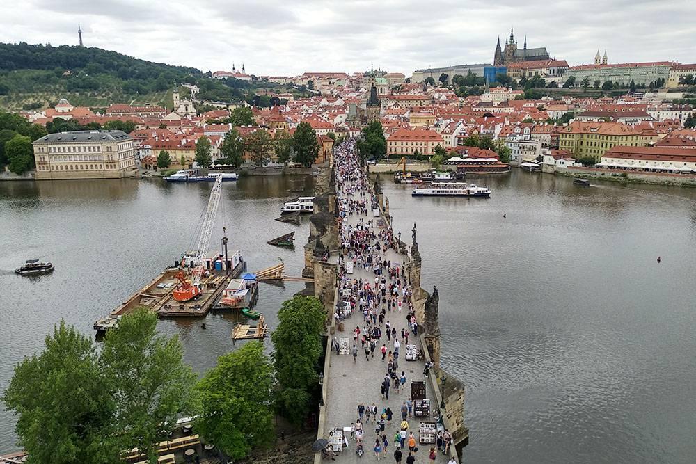 Вид на Карлов мост с башни. Справа вдалеке — Пражский Град, слева — парк на Петршином холме. Там есть смотровая вышка, розариум и планетарий. На холм можно подняться на фуникулере по обычному билету на общественный транспорт
