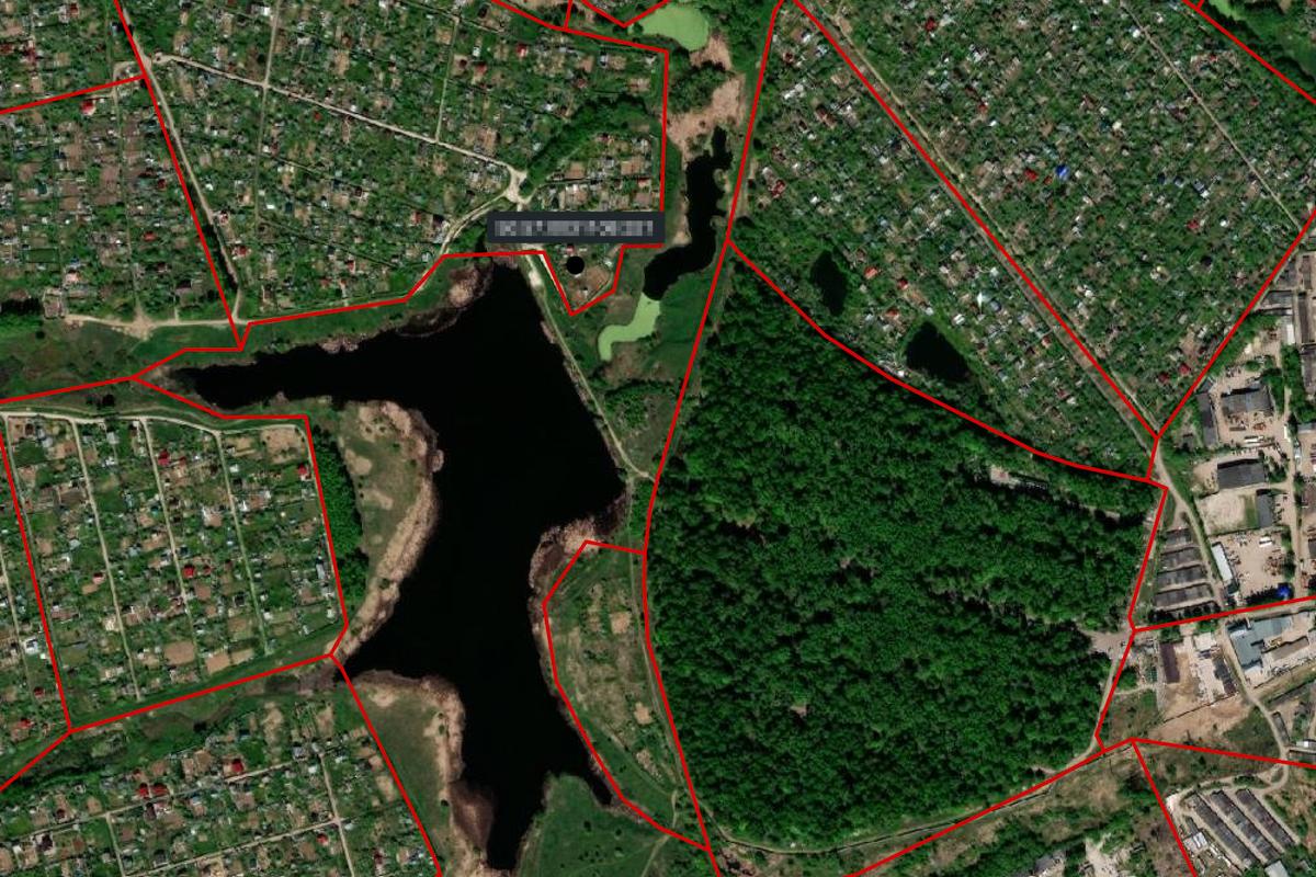 Участок расположен на берегу озера, в окружении зелени. С одной стороны, он недалеко от города и его инфраструктуры, а с другой — видно, что от городского шума и суеты его отделяет плотная зеленая зона — но не леса, а кладбища