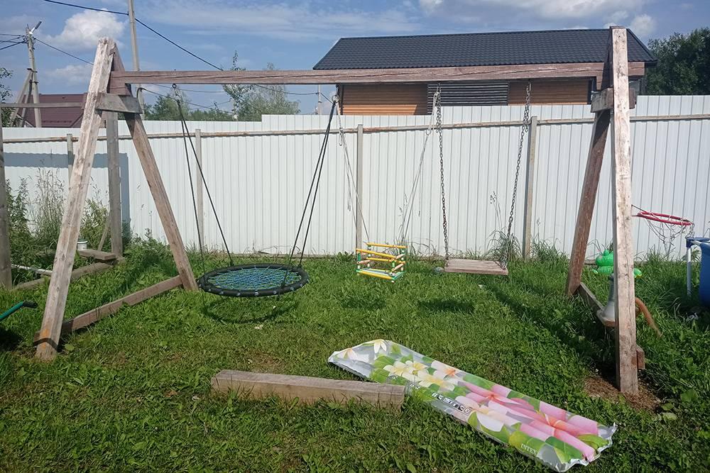 Вот так качели выглядят сейчас. Брус на траве служит скамейкой дляодного из родителей, когда маленькую дочь надо качать на пластиковом сиденье с бортиками