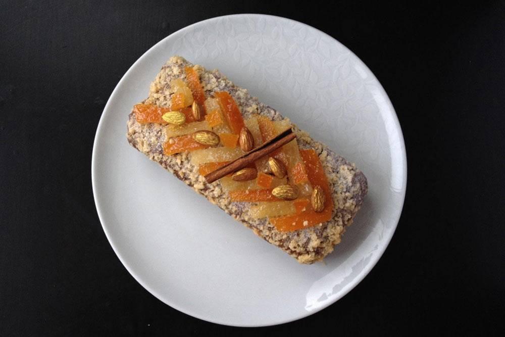 Классический кекс «Хлеб соспециями». Украшен апельсиновыми иимбирными цукатами, миндалем, покрытым золотым кандурином, и крамблом — это хрустящий слой — изминдальной муки. ВРоссии кекс какдесерт недооценен: он кажется слишком простым, хотя благодаря разным наполнителям можно добиться интересных вкусов