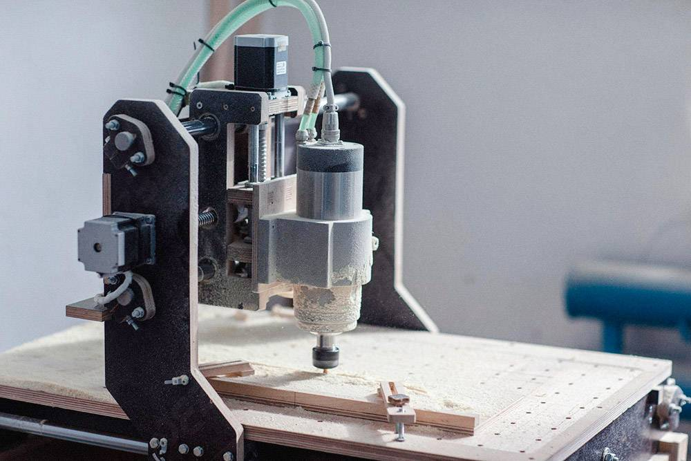 Это малый фрезерный станок с числовым программным управлением. Его используют, чтобы сделать детали с криволинейными поверхностями. Например, кобылку (деревянная подставка под струны) и лопатку (головка балалайки, на которой находится колковый механизм, необходимый для натягивания струн)