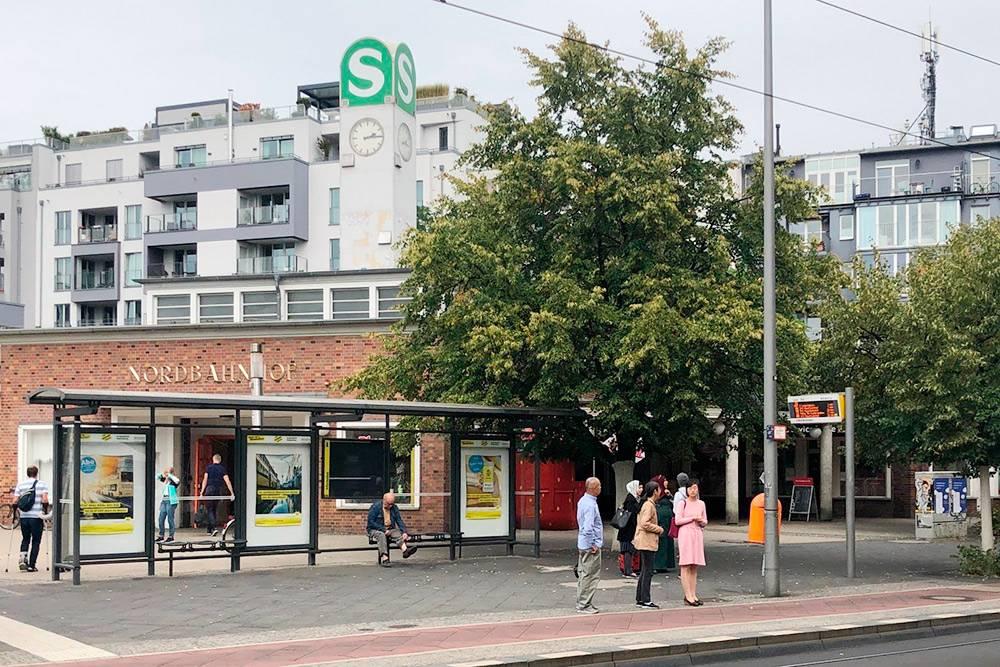 Комбинированная остановка трамвая и автобуса. Данные на табло показывают время прибытия транспорта, но они часто врут: минута на табло засчитывается за две минуты в жизни. На заднем плане — станция S-бана, городской электрички