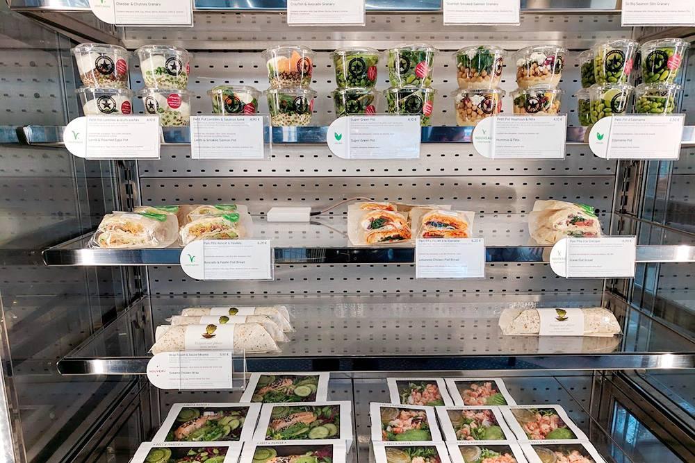 Витрина в «Прет-а-Манже». Сверху вниз: салаты с чечевицей и яйцом пашот или копченым лососем от 4,1€ (291<span class=ruble>Р</span>), пита с фалафелем и авокадо или курицей по-ливански за 6,2€ (440<span class=ruble>Р</span>), ролл с цыпленком и овощами за 5,5€ (391<span class=ruble>Р</span>), большая порция салата из авокадо, зелени и огурца с заправкой и креветками или филе лосося — 6,9€ (490<span class=ruble>Р</span>)